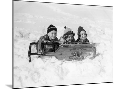 Two Girls and One Boy Lying on Belly in Snow Using Sled As Shield-H^ Armstrong Roberts-Mounted Photographic Print