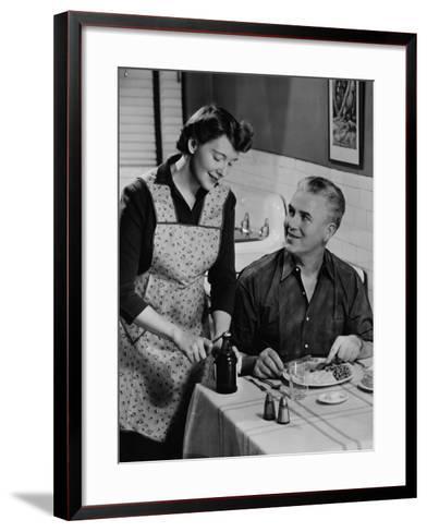 Woman Opening Beer Bottle For Man Eating Dinner-George Marks-Framed Art Print