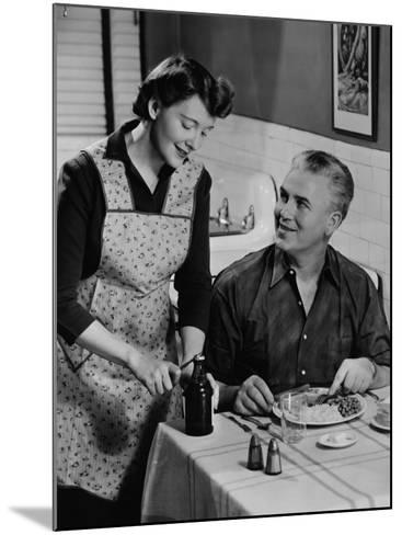 Woman Opening Beer Bottle For Man Eating Dinner-George Marks-Mounted Photographic Print