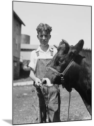 Teenage Farm Boy Wearing Bib Overalls, Holding Jersey Bull-H^ Armstrong Roberts-Mounted Photographic Print