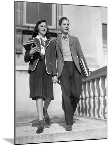 Teen Couple With Books Walking Outside School-George Marks-Mounted Photographic Print