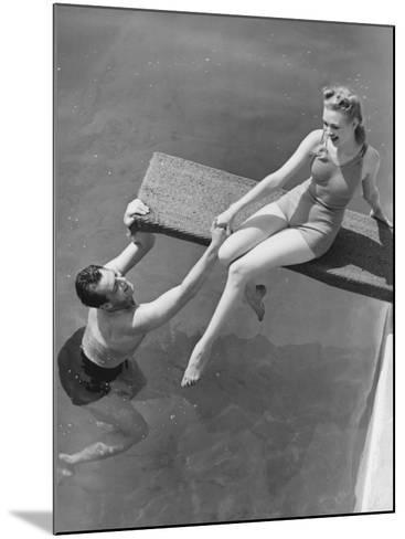 Woman Sitting on Diving Board, Man Grasping Her Hand-George Marks-Mounted Photographic Print