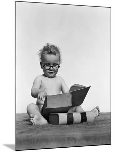 Baby Boy is Wearing Round Glasses While Reading a Very Large Book-H^ Armstrong Roberts-Mounted Photographic Print