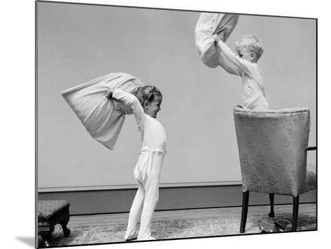 Boy and Girl Having a Pillow Fight, Boy Standing on Chair Swinging Pillow-H^ Armstrong Roberts-Mounted Photographic Print