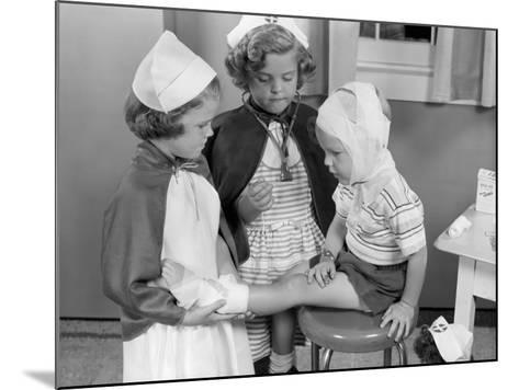 Two Young Girls Dressed As Nurses, Bandaging Three Year Old Boy's Head and Foot-H^ Armstrong Roberts-Mounted Photographic Print
