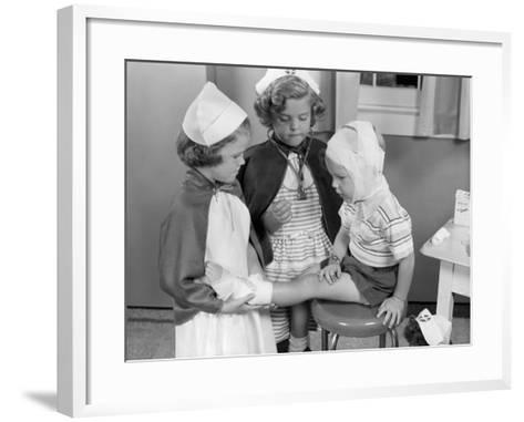Two Young Girls Dressed As Nurses, Bandaging Three Year Old Boy's Head and Foot-H^ Armstrong Roberts-Framed Art Print