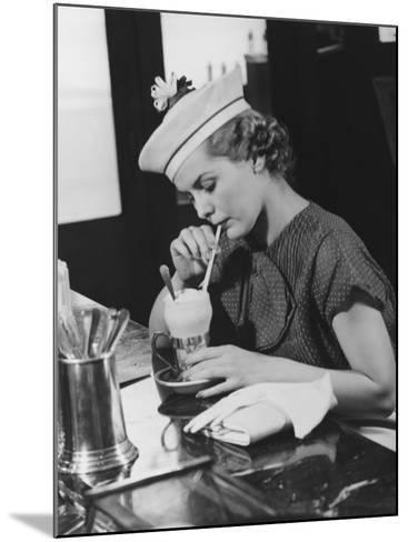 Young Woman in Fancy Hat Drinking Ice Cream Soda-George Marks-Mounted Photographic Print