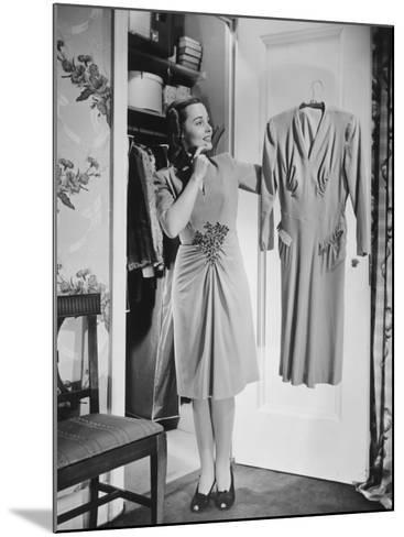 Woman Holding Dress at Opened Doors of Dressing-Room-George Marks-Mounted Photographic Print