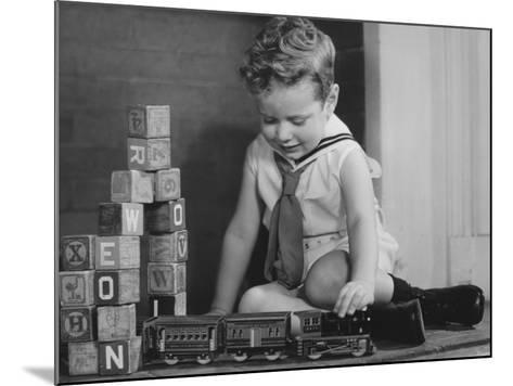 Boy (4-5) Playing With Model Train Set on Floor,-George Marks-Mounted Photographic Print