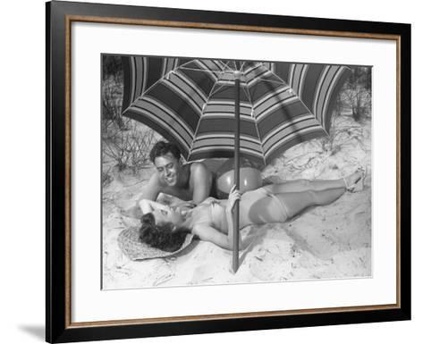 Young Couple Under Beach Umbrella-George Marks-Framed Art Print