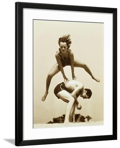 Young Couple Playing Leapfrog at Beach--Framed Art Print