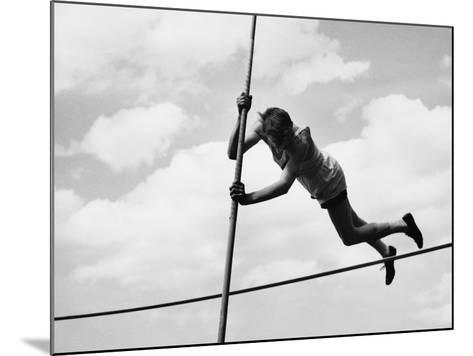 Male Pole-Vaulter Clearing Bar--Mounted Photographic Print