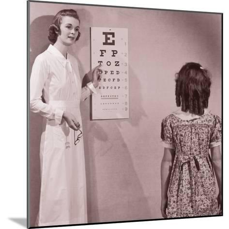 Healthcare Worker Giving Girl (8-10) Eye Examination--Mounted Photographic Print