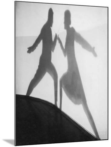 Shadow of Man and Woman Fencing--Mounted Photographic Print