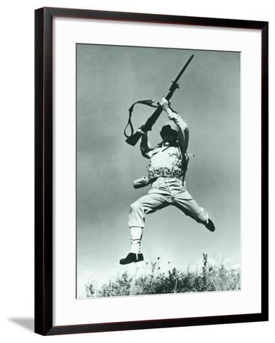 Soldier Jumping With Rifle, Low Angle View--Framed Art Print