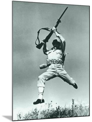 Soldier Jumping With Rifle, Low Angle View--Mounted Photographic Print
