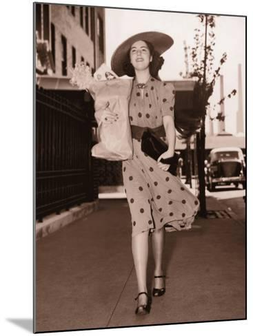 Woman Walking Down Street Carrying Grocery Parcel--Mounted Photographic Print