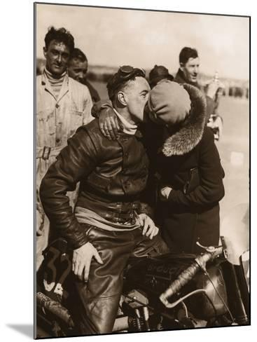 Woman Kissing Motorcycle Racer--Mounted Photographic Print