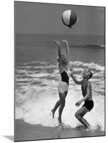 Young Couple Playing With Beach Ball at Water's Edge--Mounted Photographic Print