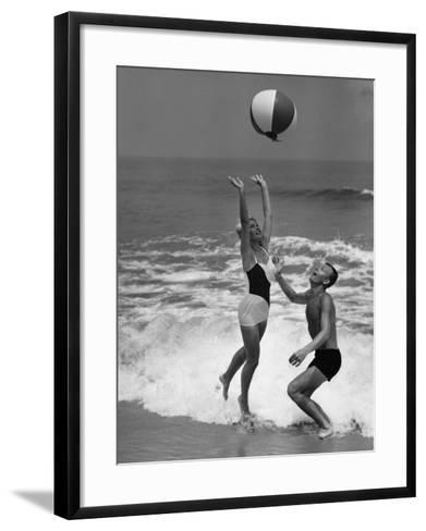 Young Couple Playing With Beach Ball at Water's Edge--Framed Art Print