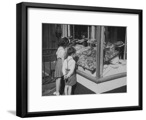 Boy and Girl Looking in at Bakery Window--Framed Art Print