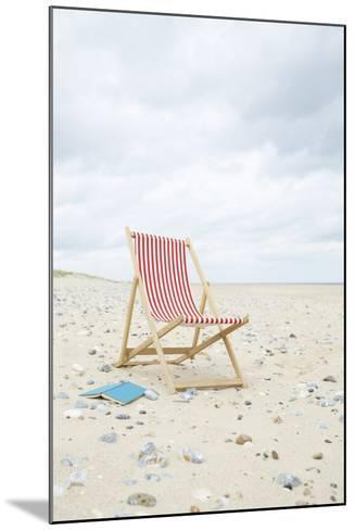Deck Chair with Book on Sand at Beach.-Dougal Waters-Mounted Photographic Print