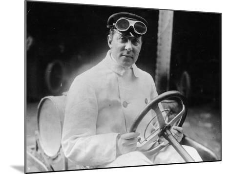 A Man at the Wheel of His Car Dressed in a Driving Coat and Goggles--Mounted Photographic Print