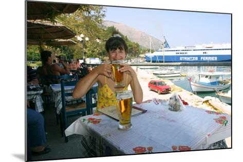 Woman Enjoying a Drink in a Harbourside Taverna, Poros, Kefalonia, Greece-Peter Thompson-Mounted Photographic Print