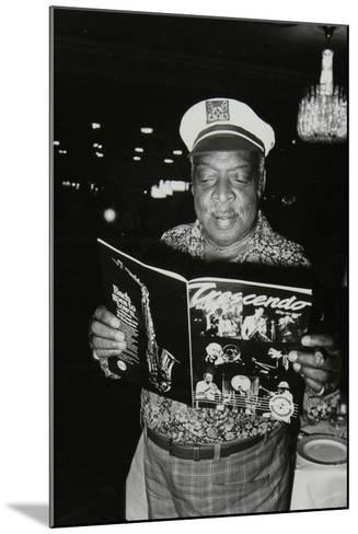 Count Basie Reading a Copy of Crescendo Magazine at the Grosvenor House Hotel, London, 1979-Denis Williams-Mounted Photographic Print