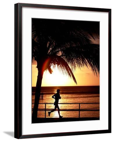 A Afternoon Runner Passes Under a Palm Tree as the Sun Sets Behind--Framed Art Print