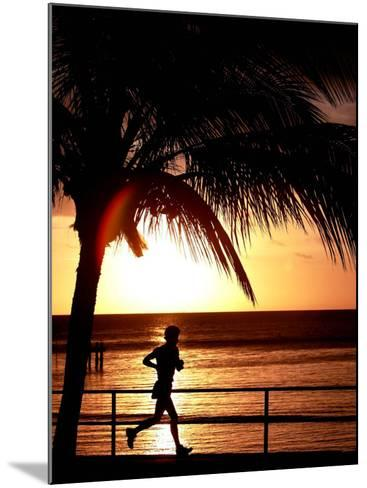 A Afternoon Runner Passes Under a Palm Tree as the Sun Sets Behind--Mounted Photographic Print