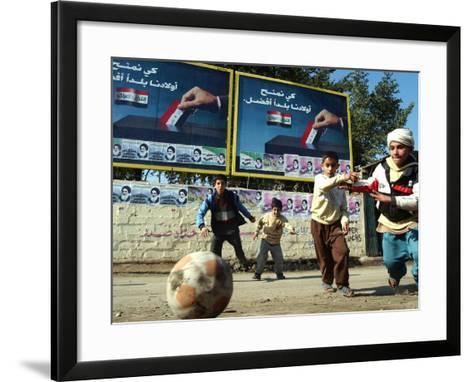 "Iraqi Boys Play Soccer Below the Poster Reading ""To Grant Iraqi Children Better Iraq""--Framed Art Print"