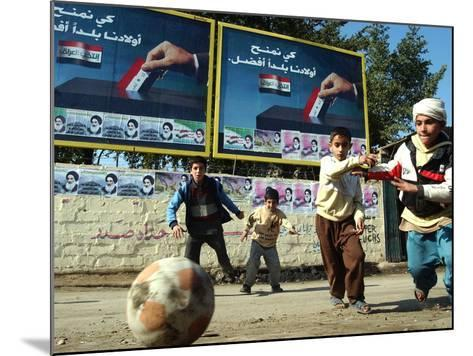 """Iraqi Boys Play Soccer Below the Poster Reading """"To Grant Iraqi Children Better Iraq""""--Mounted Photographic Print"""