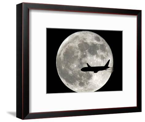 A Jet Plane Passes in Front of the Full Moon Above Surfside, Fla.--Framed Art Print