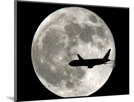 A Jet Plane Passes in Front of the Full Moon Above Surfside, Fla.--Mounted Photographic Print