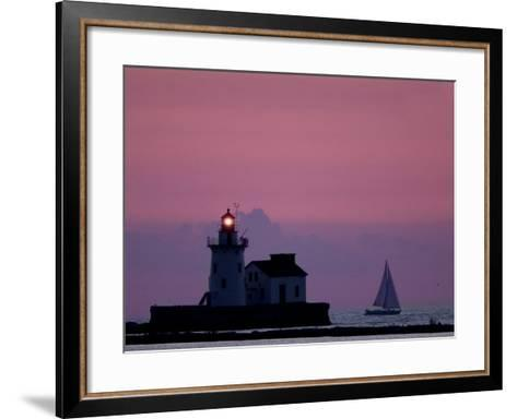 A Sailboat Slips Past a Lighthouse as the Sunset Comes to Lake Erie off the Coast of Cleveland--Framed Art Print