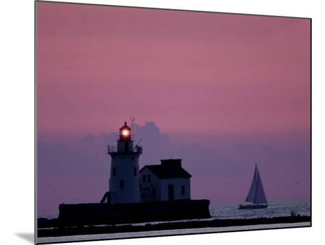 A Sailboat Slips Past a Lighthouse as the Sunset Comes to Lake Erie off the Coast of Cleveland--Mounted Photographic Print
