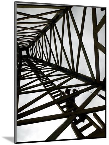 A Reenactor is Silhouetted Inside a Replica of the Spindletop Oil Derrick--Mounted Photographic Print