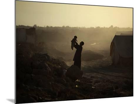 Displaced Man Holds His Baby Next to His Tent in Jalozai Refugee Camp Near Peshawar, Pakistan--Mounted Photographic Print