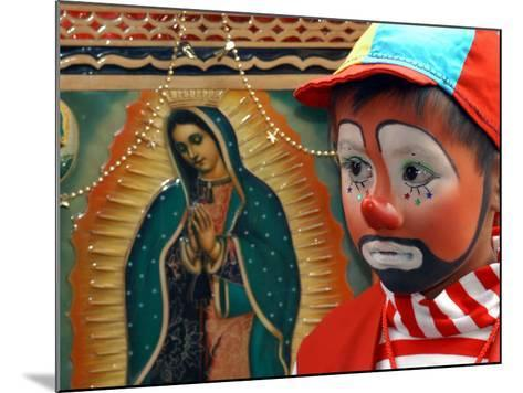 """Young Clown, """"Bolillito,"""" Stands Next to an Image of the Virgin of Guadalupe in Mexico City--Mounted Photographic Print"""