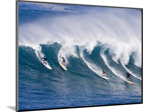 Surfers Ride a Wave at Waimea Beach on the North Shore of Oahu, Hawaii--Mounted Photographic Print