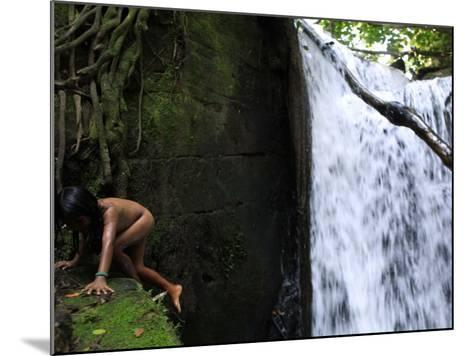 Child from the Ache Indigenous Group Plays Near a Waterfall in Cerro Moroti, Paraguay--Mounted Photographic Print