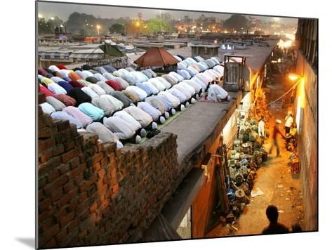 Indian Muslims During Friday Evening Prayers on the Rooftop of a Building over an Auto Parts Market--Mounted Photographic Print