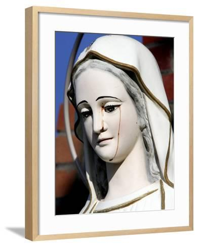 Red Stains are Seen Running from the Left Eye of a Statue of the Virgin Mary--Framed Art Print