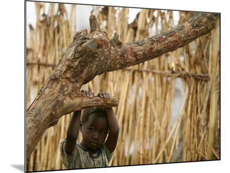 A Sudanese Girl Plays Inside a Thatched Hut at the Refugee Camp of Zamzam--Mounted Photographic Print
