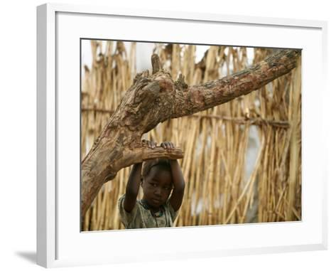 A Sudanese Girl Plays Inside a Thatched Hut at the Refugee Camp of Zamzam--Framed Art Print