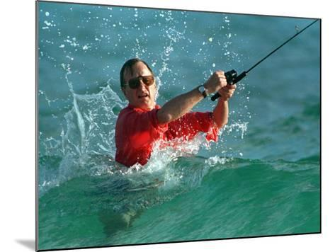 Waves Splash President-Elect George Bush as He Casts a Line While Surf-Fishing--Mounted Photographic Print