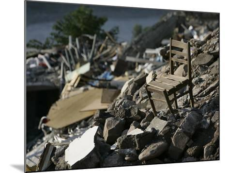 A Chair is Seen on the Rubble of a Collapsed Apartment Complex--Mounted Photographic Print