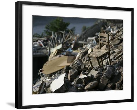 A Chair is Seen on the Rubble of a Collapsed Apartment Complex--Framed Art Print