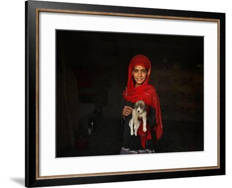 Girl Holds a Puppy as the Sun Sets over Kabul's Impoverished Teppe Maranjan Neighborhood--Framed Art Print